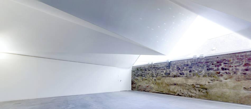 Multifunktionaler Innenraum mit Blick auf die historische Bruchsteinmauer